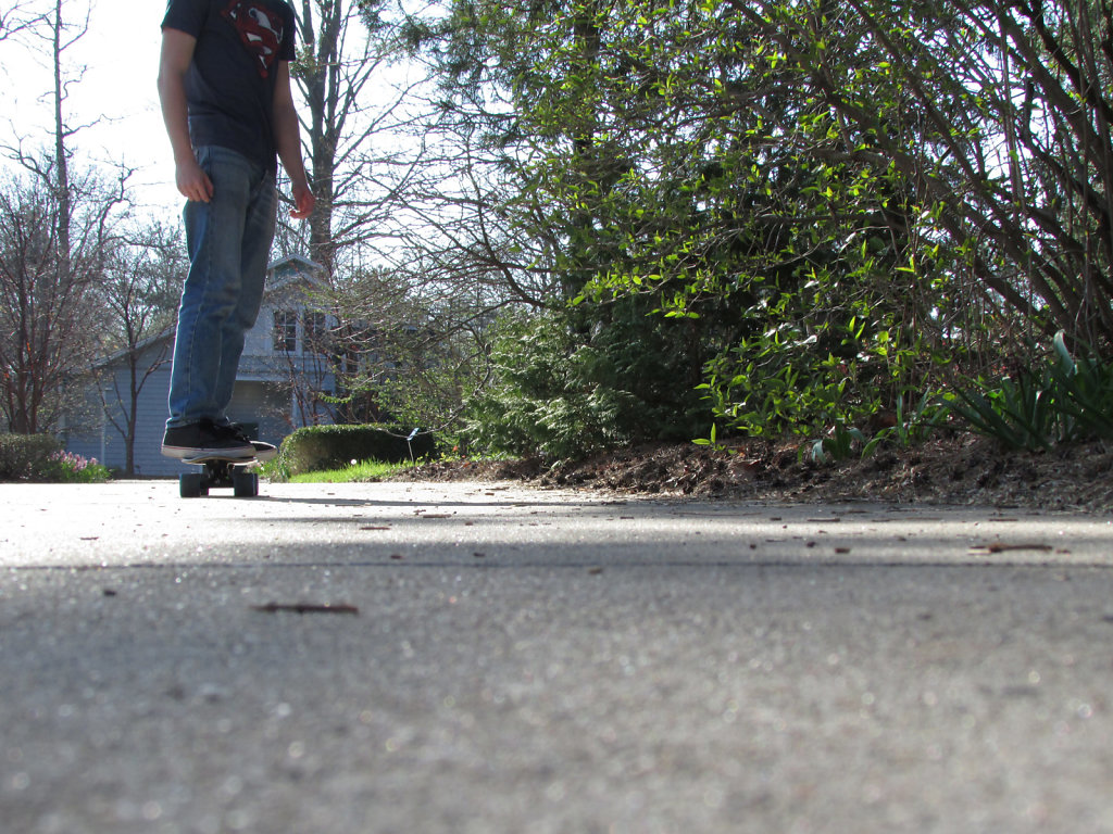 Young man skateboarding on a sidewalk in late spring
