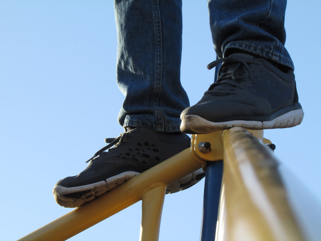 Feet on top of metal playground equipment