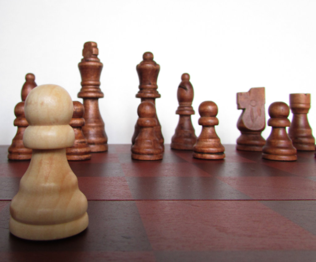 White wooden chess pawn advancing a space