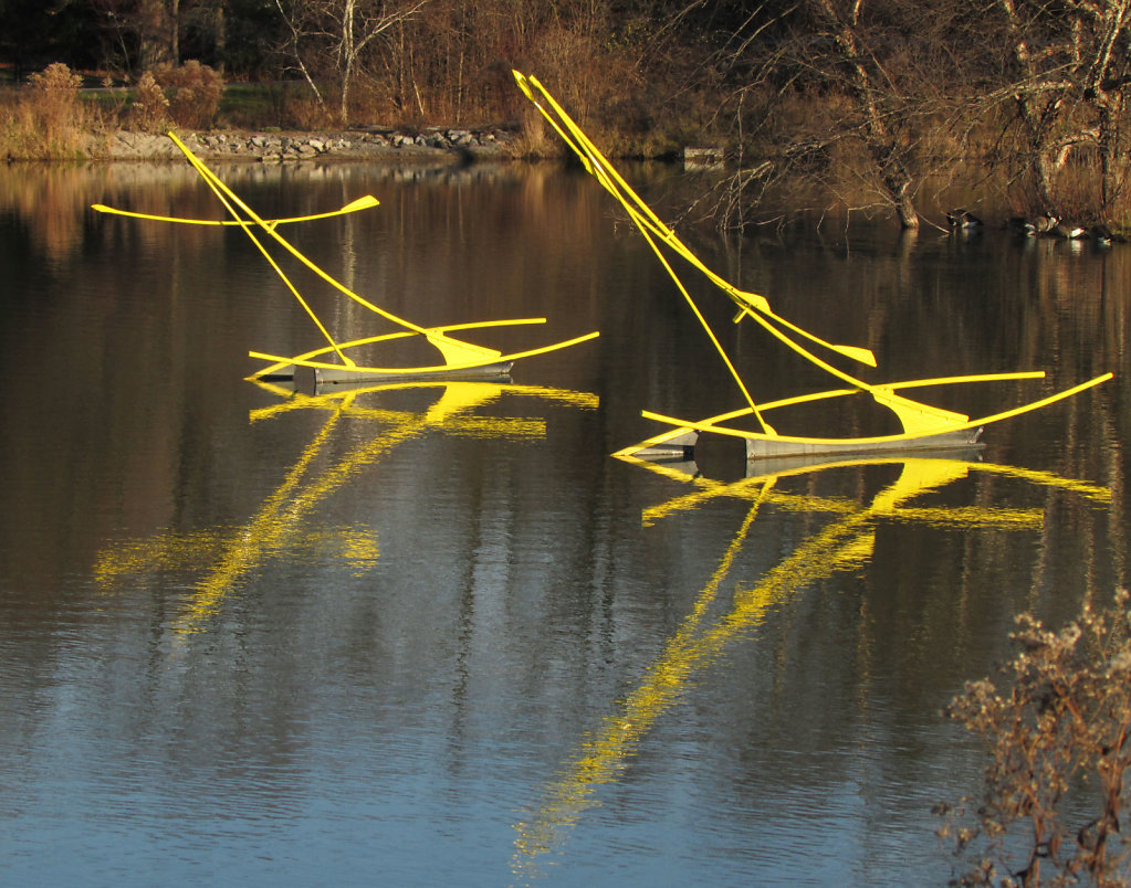 Bright yellow metal sculptures rising from the water