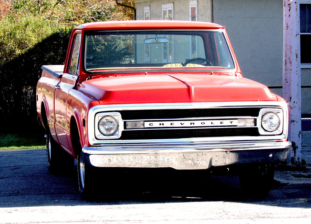 Old red Chevrolet truck in a parkinglot