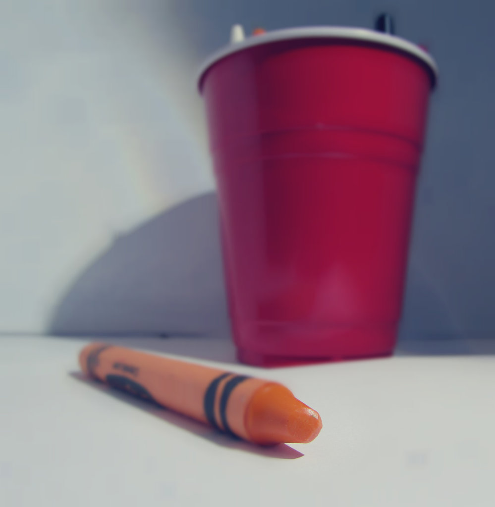 Orange crayon outside of cup